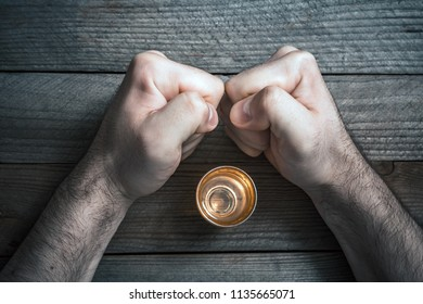 Quit Alcohol Drinking Concept With A Booze Glass Surrounded By 2 Stressed Looking Clenched Fists