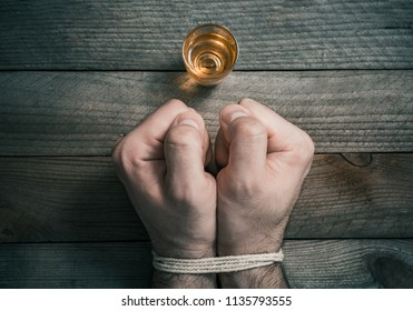 Quit Drinking Alcohol Concept With A Booze Glass In Front Of 2 Tied Stressed Looking Clenched Fists