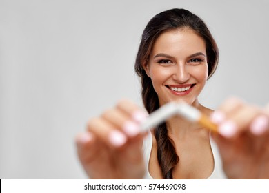 Quit Smoking. Closeup Of Beautiful Happy Female Breaking Cigarette. Portrait Of Smiling Woman Holding Broken Cigarette In Hands. Healthy Lifestyle Concept. High Resolution