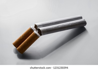 Quit smoking concept, two cigarettes as a double barrel shotgun over gray background with copy space
