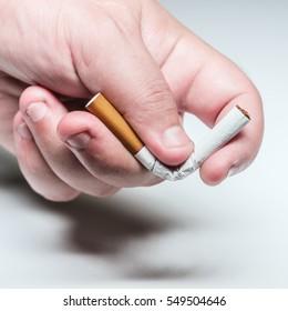 Quit smoking conceptual image male hand bending a cigarette