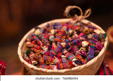 Quitapenitas-  colorful Guatemalan Worry Dolls in a basket.