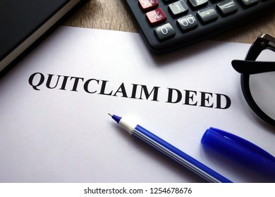 Quitclaim deed form, pen, glasses and calculator on desk
