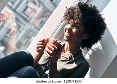 Quite contemplation. Attractive young African woman holding a cup and smiling while sitting on window sill indoors
