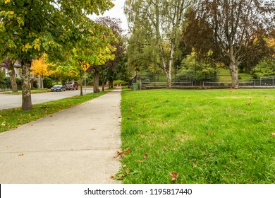 A quite residential sidewalk and park with a tennis court in the fall. Vancouver's Kitsilano neighbourhood.