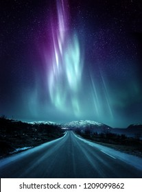 A quite road in Norway with a spectacular Northern Light Aurora display lighting up the night sky above the mountains. A popular destination within the arctic circle for hunting the Northern Lights.