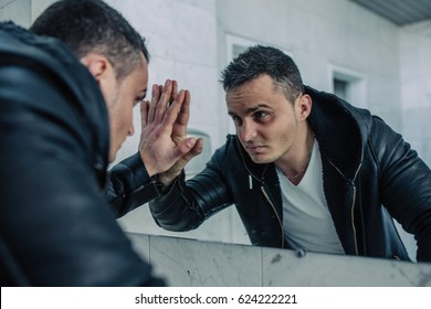Quite wealthy man with the beaten looks at themselves in a mirror and looks in the face. On him expensive black coat and a white t-shirt. The man has a fighting look.