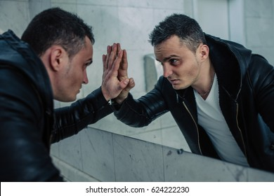 Quite wealthy man in a public toilet with the beaten person looks in a mirror. He looks to himself in the face, as in soul.