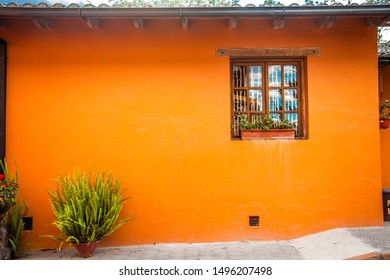 QUITO, ECUADOR - 6 DECEMBER 2015: Orange wall made of adobe and cement, with a rustic-style window, which is part of a colonial house located in the parish of San Antonio north of the city of Quito.