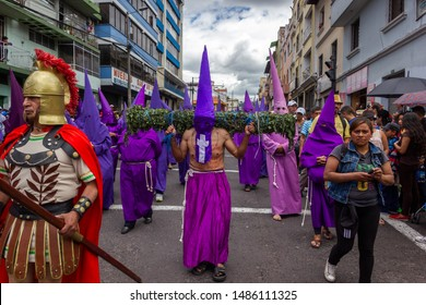 QUITO, ECUADOR - APRIL 3, 2015: 'Cucurucho' carrying a wooden log rolled up with nettle with text in his chest in Good Friday Procession.