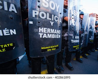Quito, Ecuador - April 7, 2016: Police awaiting overlooking peaceful anti tax march in Shyris Avenue, beautiful blue sky and buildings background