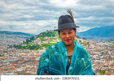 QUITO, ECUADOR - APRIL 8, 2019: Portrait of a smiling indigenous Otavalo lady in front of the historic city center of Quito in the Andes mountain range.