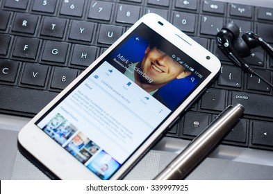 QUITO, ECUADOR - AUGUST 3, 2015: White smartphone closeup lying next to silver pen on laptop keyboard with Mark Zuckerberg Facebook profile screen visible.