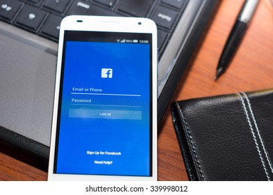 QUITO, ECUADOR - AUGUST 3, 2015: White smartphone closeup lying on laptop corner with Facebook website screen visible, eaplugs mouse and pen blurry background, business communication concept.