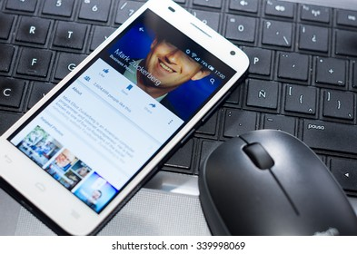 QUITO, ECUADOR - AUGUST 3, 2015: White smartphone closeup lying next to silver pen on laptop keyboard with Mark Zuckerberg Facebook profile screen visible.