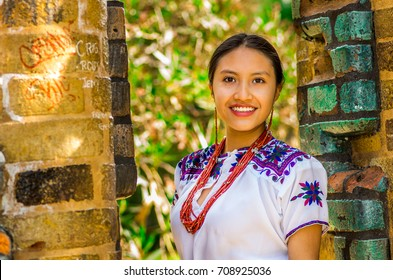 QUITO, ECUADOR - AUGUST, 30 2017: Portrait of a young indigenous woman wearing a typical andean clothes, posing for camera in front of an old wall, in the park