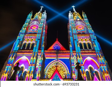 QUITO, ECUADOR - AUGUST 9, 2017: The neo - gothic style Basilica of the National Vow (Basilica del Voto Nacional) illuminated with colorful lights during the Quito light festival.