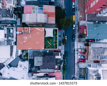 Quito, Ecuador - Feb 2019: Aerial DRONE shot of tourists swinging on hammock, relaxing on rooftop of skyscrapper hotel. Interior design. View of local street, road and buildings surrounding.