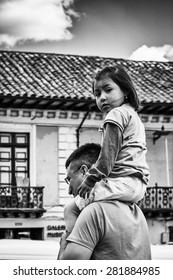 QUITO, ECUADOR - JAN 2, 2015: Unidentified Ecuadorian girl on her fathers shoulders. 71,9% of Ecuadorian people belong to the Mestizo ethnic group