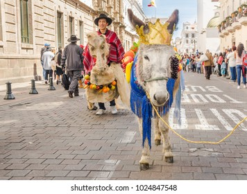 Quito, Ecuador - January 11, 2018: Outdoor view of unidentified people wearing colorful clothes and a donkey with a crown in the head and walking in the streets during a parade in Quito, Ecuador