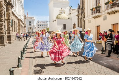 Quito, Ecuador - January 11, 2018: Outdoor view of unidentified people wearing beautiful dresses and straw hats, dancing in the streets during a parade in Quito, Ecuador