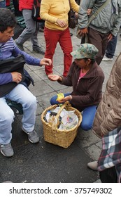 QUITO, ECUADOR - JANUARY 24, 2016: President Rafael Correa addresses crowd from the presidential palace.  Woman sells food from a basked to the crowd in the park below