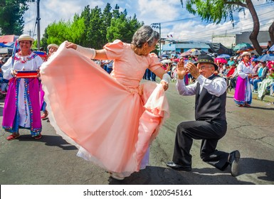 Quito, Ecuador - January 31, 2018: Outdoor view of unidentified old people, woman wearing a pink dress and dancing in the streets with his man during a parade in Quito, Ecuador
