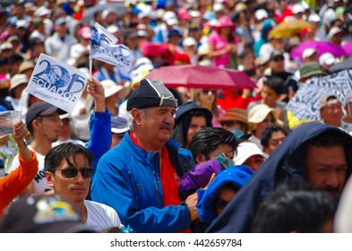 QUITO, ECUADOR - JULY 7, 2015: In the middle of thousand people, a big man with blue pull is praying, holding a jacket
