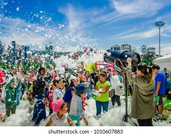 QUITO, ECUADOR- NOVEMBER, 28, 2017: Outdoor view of woman with foam machine and unidentified people enjoying and dancing at a foam party at Quito festival