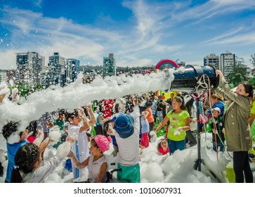 QUITO, ECUADOR- NOVEMBER, 28, 2017: Beautiful and fun view of woman with foam machine and group of children enjoying and dancing at a foam party at Quito festival