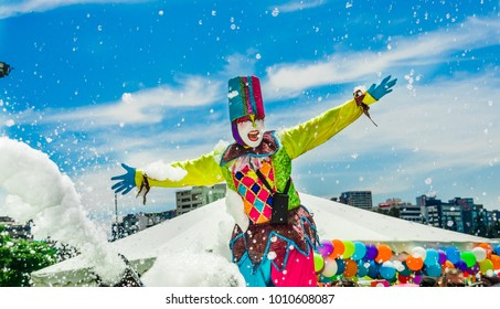 QUITO, ECUADOR- NOVEMBER, 28, 2017: Close up of unidentified person wearing a clown costume surrounding of group of children having fun and dancing at a foam party at Quito festival