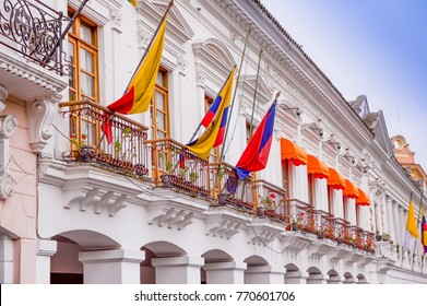 QUITO, ECUADOR NOVEMBER, 28, 2017: white building with some glags hanging from a balcony at historical center of old town Quito in northern Ecuador in the Andes mountains