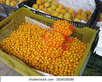 Quito, Ecuador November 7, 2014: golden berries (also Uvilla) in a green crate at a market. Also three net packs of golden berries in the crate