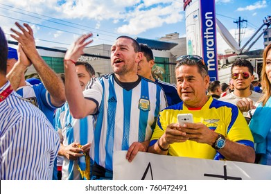 QUITO, ECUADOR - OCTOBER 11, 2017: Close up of Argentina fans wearing there official football shirts and supporting their team in outdoors, screaming and jumping