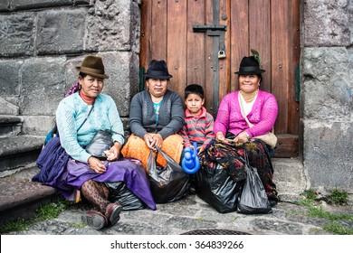 QUITO, ECUADOR, SEP 01, 2014:  Portrait of an unknown indigenous Ecuadorian family resting at  Plaza de San Francisco in Quito.