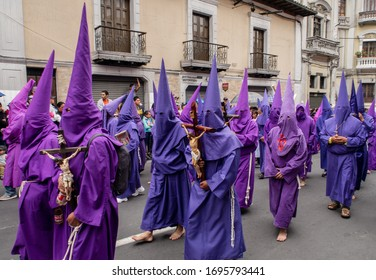 Quito, Pichincha, Ecuador - March 27, 2018: March of the Penitents at Good Friday procession at easter,  Semana Santa, in Quito. Cucuruchos wearing purple costumes of catholic practice.