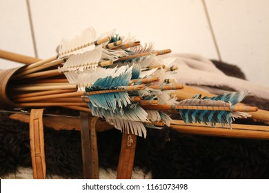A quiver of arrows with white and blue feathers.