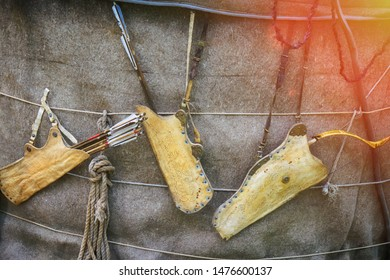 Quivers with vintage bows hanging on the wall. Weapons for hunting and tribal wars of ancient times.
