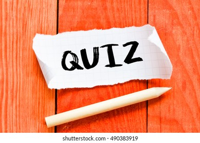 Quiz./ Note with quiz on the wooden background