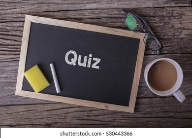 Quiz On blackboard with cup of coffee, with glasses on wooden background