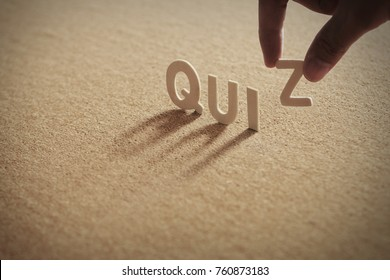 QUIZ wood word on compressed or corkboard with human's finger at Z letter.