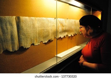 QUMRAN, ISRAEL - DEC 14 2008:Woman looks at the Dead Sea Scrolls on display at the caves of Qumran.The Dead Sea Scrolls were discovered in Qumran caves between the years 1947 and 1956.