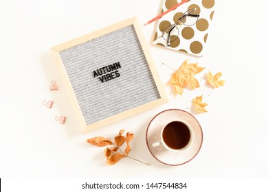 Quote Autumn vibes. Flatlay of letterboard, glasses, stationery, notepad, mug of coffee on white desk