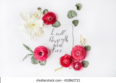 "quote ""Do small things with great love"" written in calligraphy style on paper with pink, red roses, ranunculus,   white tulips and green leaves isolated on white background. Flat lay, top view"