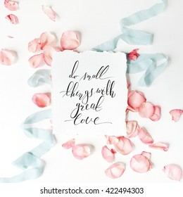 "quote ""Do small things with great love"" written in calligraphy style on paper with pink petals and blue ribbon, flat lay composition"