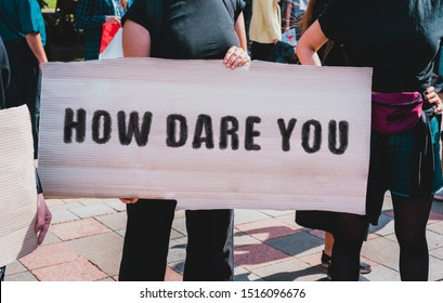"Quote of Greta Thunberg "" How dare you "" drawn on a carton banner in hand. Movement against the climate change. A girl holds a cardboard with an inscription. Rally. Protest"