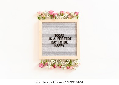 Quote Today is a perfect day to be happy. Letterboard with frame made of flowers on white background