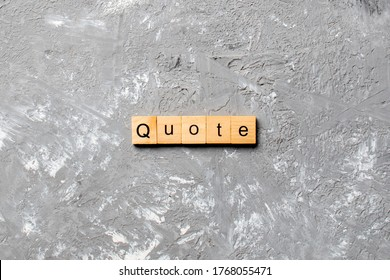 Quote word written on wood block. Quote text on cement table for your desing, concept.