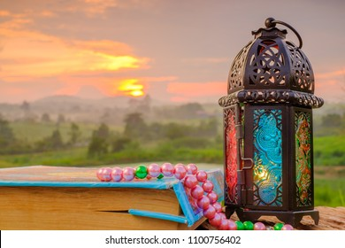 Quran  , beads. and lantern on an old wood with a beautiful sunrise as background. Ramadhan Concept. Quran with Arabic calligraphy means ''Quran Kareem '', the Qur'an is the holy book of Islam.