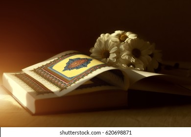 Quran - the holy book of islam open  with flowers in  sunrays